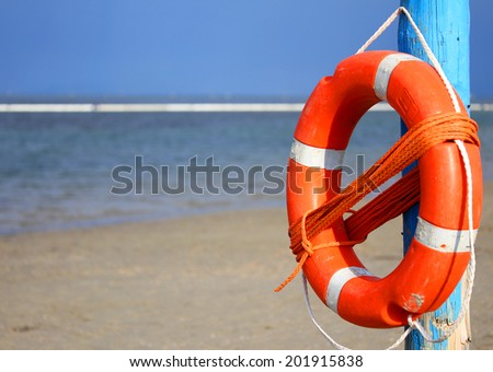 pole with orange lifejacket at sea on the beach 2