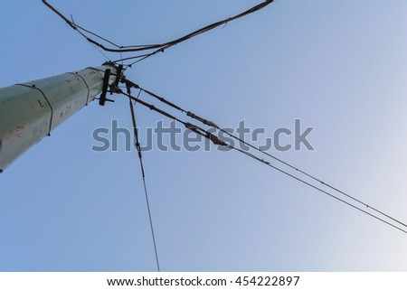 pole with wires attached to it intersect at different angles against the sky