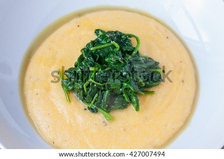 Polenta topped with wilted fresh spinach served in a white bowl - stock photo