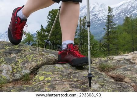 Poles and hiking boot closeup on mountain rocks - stock photo