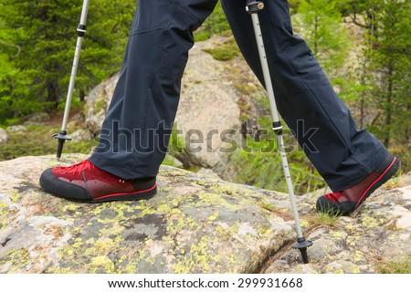 Poles and hiking boot closeup on mountain rocks, nordic walking, hiking. - stock photo