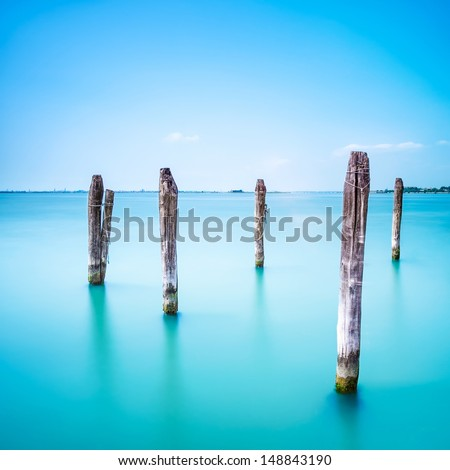 Poles and soft water on Venice lagoon. Long exposure photography. - stock photo