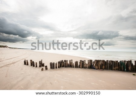 Poles in the sand at the beach in Tversted in Denmark - stock photo