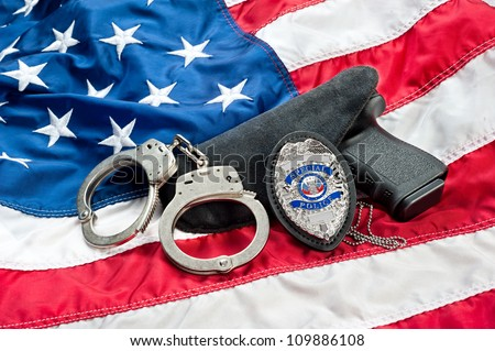 Police badge, gun and handcuffs on an American flag symbolizing law enforcement in the United States. - stock photo