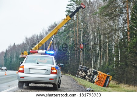 police car with a flasher in front of damaged lorry trailer in ditch of highway - stock photo