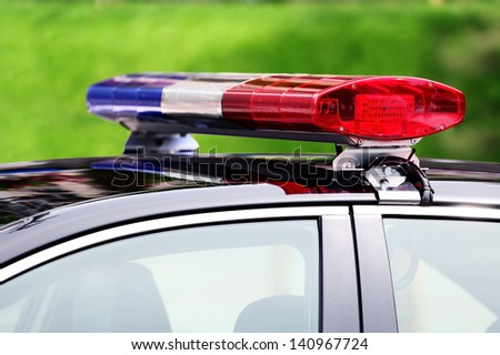 police car with siren light closeup on green background, selective focus - stock photo