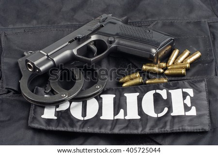 Police concept - handgun on black uniform background  - stock photo