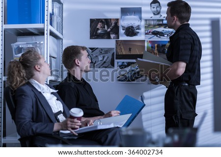 Police cooperating with private detective during investigation - stock photo