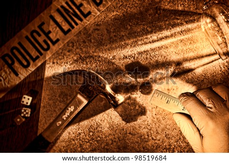 Police forensic investigator with glove on hand holding a technician measuring ruler at CSI gruesome murder crime scene with hammer weapon and victim blood evidence during a criminal law investigation - stock photo