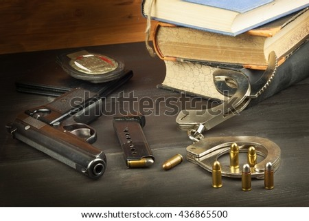 Police gun and badge. Weapons to defend law and order. The right to own a gun. Defense Law. Ombudsmen. Crime and Punishment. - stock photo