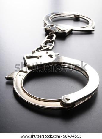 police handcuffs on black background showing law concept