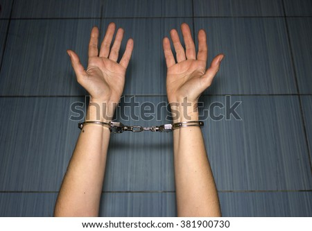 police handcuffs on the hands of women criminals and crimes - stock photo