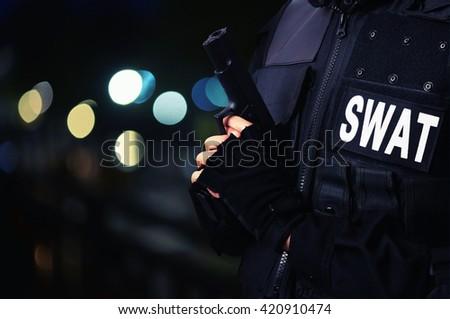 police hold gun at night - stock photo