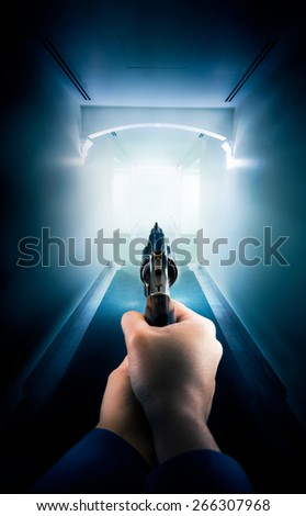 Police in a hallway holding a gun / dramatic lighting - stock photo