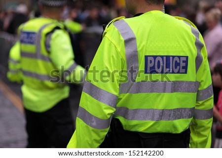 Police in hi-visibility jackets policing crowd control at a UK event - stock photo