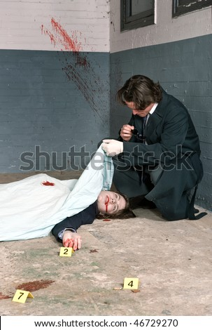 Police inspector examining a dead body, biting on his glasses, deep in thought - stock photo