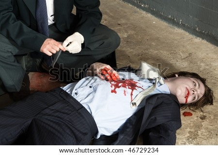 Police inspector hovering over a murdered businessman - stock photo