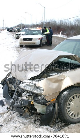 Police investigate a car wreck on an icy road.