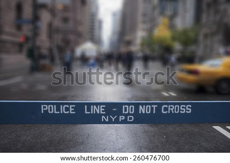 Police Line Do Not Cross. A Police line do not cross police department crime scene sign on the sidewalk in New York City. Blur background. - stock photo