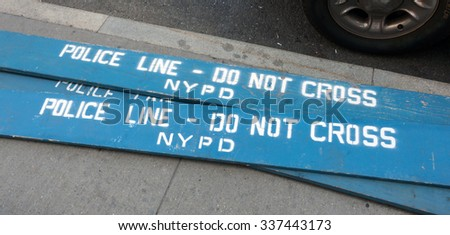 Police Line Do Not Cross. A Police line do not cross police department crime scene sign on the sidewalk in New York City.