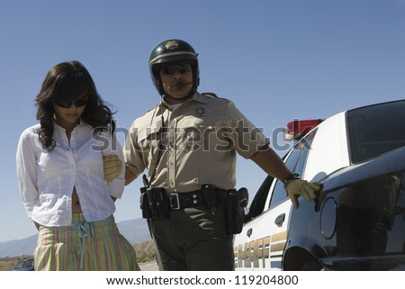 Police man arresting young woman on road - stock photo