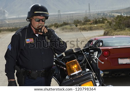 Police man communicating on walkie-talkie with car in the background - stock photo