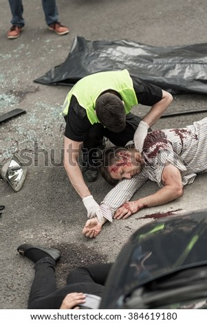 Police man is checking if anyone survived car accident - stock photo