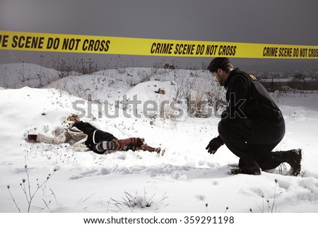 Police man watching place of murder in winter nature - stock photo