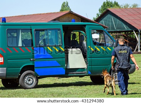 Police man with his dog next to the patrol car - stock photo