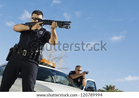 Police officer aiming with gun by car - stock photo