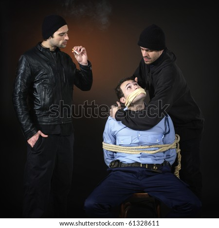 Police officer and two thiefs, they have captured him and tied him down. Dark background. Square format.