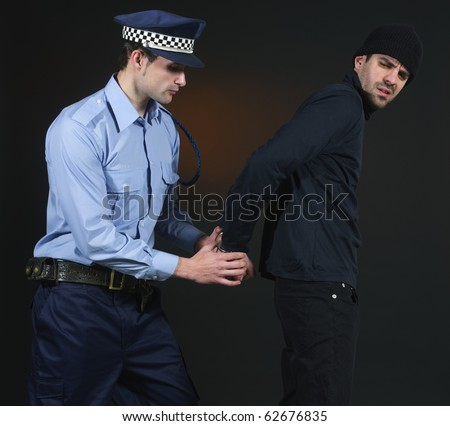 Police officer arresting a thief. Dark background. - stock photo