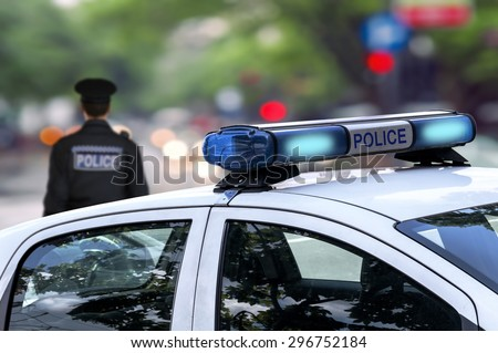Police officer emergency service car driving street with siren light blinking  - stock photo