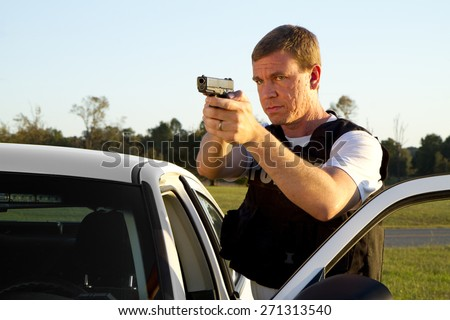 Police officer gun drawn, looks over open door - stock photo