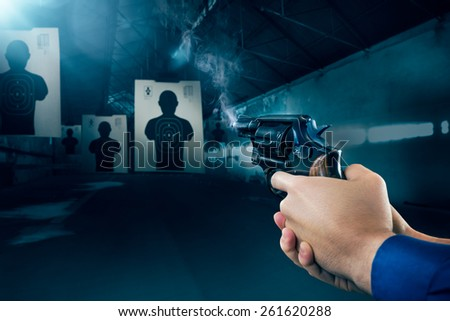 Police officer holding a gun at a shooting range - stock photo
