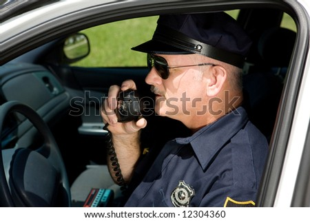 Police officer in squad car talking on his radio.  Closeup view. - stock photo