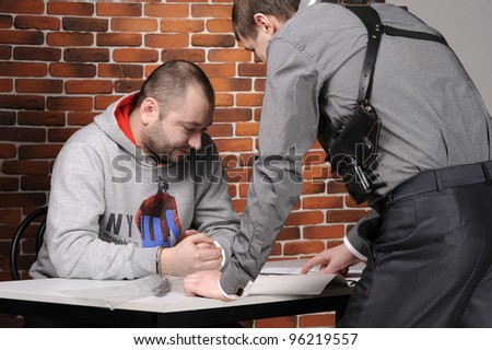 Police officer interrogates detainee against a break wall
