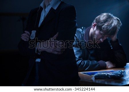 Police officer is waiting for a confession - stock photo