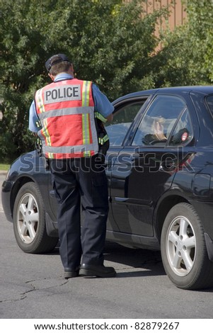 Police officer issuing speeding ticket - stock photo