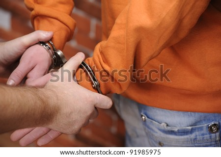 police officer puts handcuffs on detainee near brick wall
