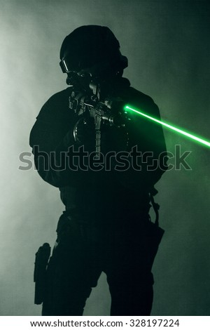 Police officer SWAT in black uniform in the smoke with laser sights - stock photo