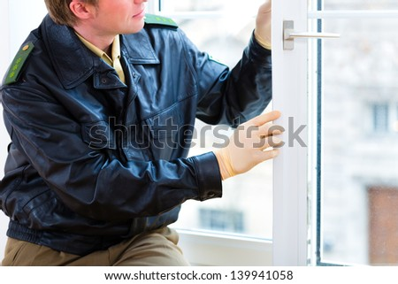 Police officer takes evidence on window after burglary - stock photo