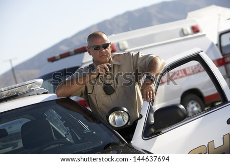 Police officer using two way radio by police car with ambulance in background - stock photo