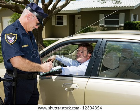 Police officer writing a traffic citation while an unfortunate driver looks on from his car. - stock photo