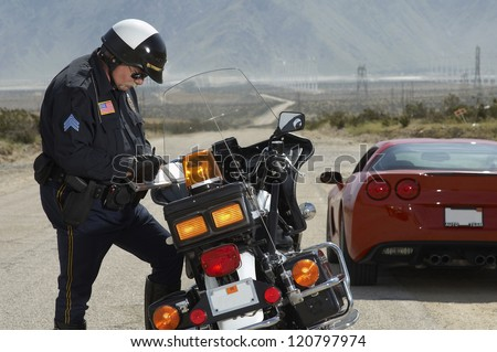 Police officer writing ticket by bike with car in the background - stock photo