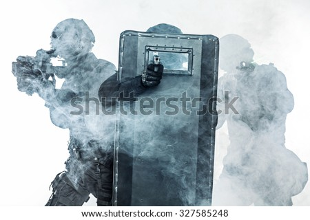 Police officers SWAT with ballistic shield in the smoke studio shot - stock photo