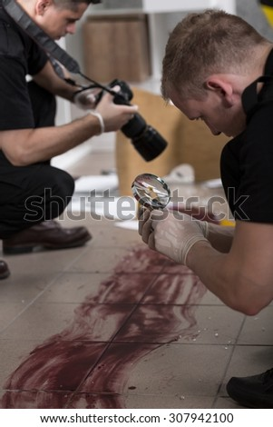 Police officers working at the murder scene - stock photo