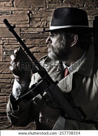 Police or Gangster, on a wall, carrying a submachine gun