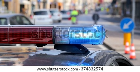 police patrol car with blue sirens during a traffic control in the metropolis - stock photo