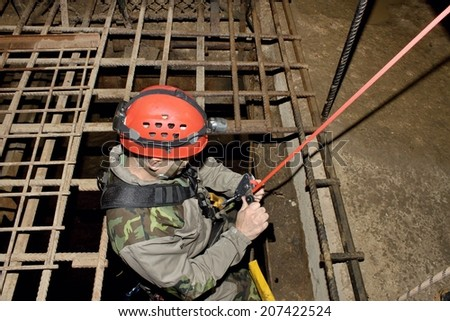 Police rescue worker runs the rope into the flooded old mine - stock photo